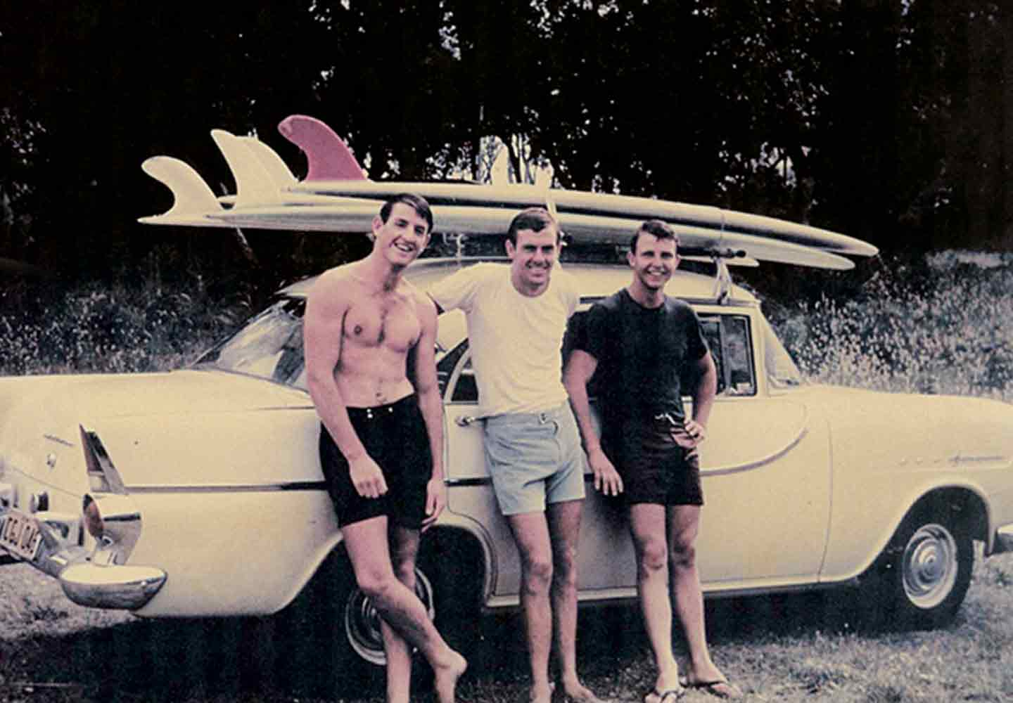 vintage photo of three surfers standing by a car